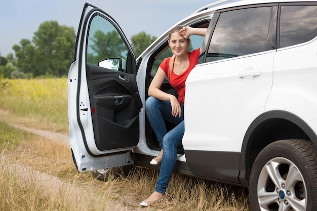 Schöne lächelnde fahrerin, die sich im auto auf dem feld entspannt
