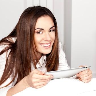 Schöne lächelnde frau auf sofa mit tablette