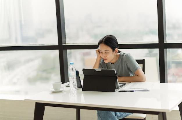 Schöne lächelnde frau bei einem videoanruf auf ihrem tablet während der arbeit im büro