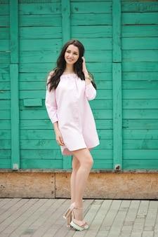 Schöne lächelnde frau. brünette geht in einem rosa kurzen kleid die straße entlang