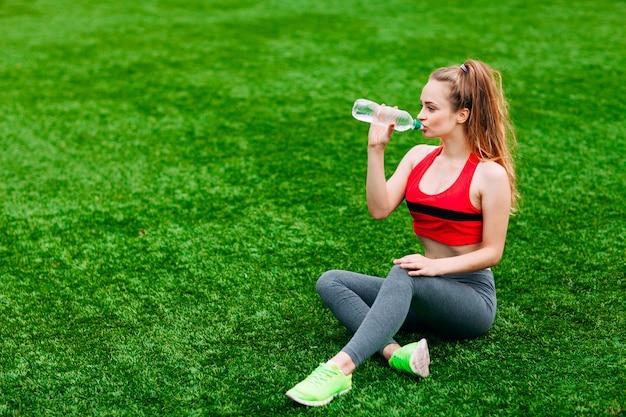 Schöne lächelnde frau, die auf dem gras im park während des trainings sich entspannt. sport- und fitnesskonzept