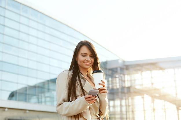 Schöne lächelnde frau, die auf nahem büro von der arbeit mit kaffeetasse und sms auf handy übergeht. telefonkommunikation.
