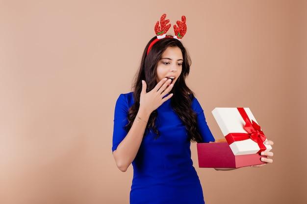 Schöne lächelnde frau, die geschenkbox hält und das lustige weihnachtsband lokalisiert über braun trägt