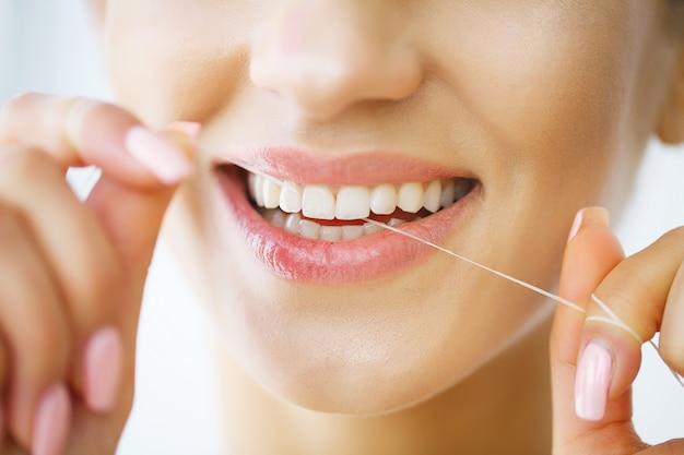 Schöne lächelnde frau, die gesunde weiße zähne flossing ist.