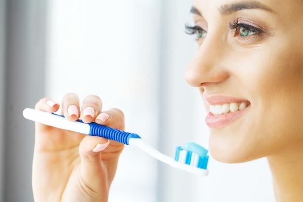 Schöne lächelnde frau, die gesunde weiße zähne mit bürste putzt. bild mit hoher auflösung