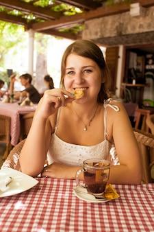 Schöne lächelnde frau, die im café im freien sitzt und keks isst