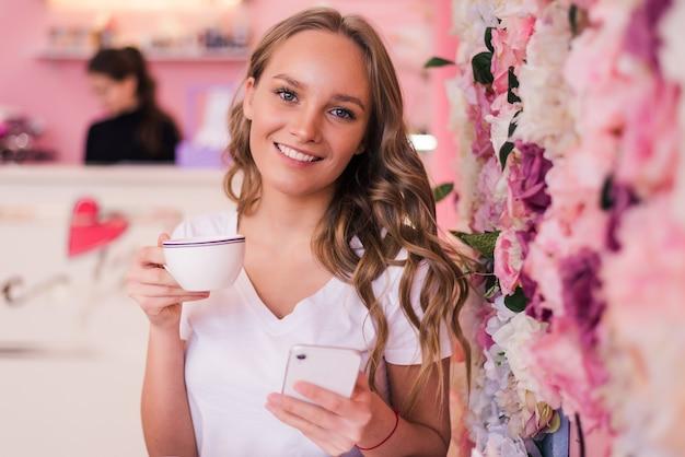 Schöne lächelnde frau, die kaffee im café trinkt. porträt der reifen frau in einer cafeteria, die heißen tee trinkt