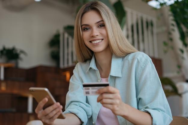 Schöne lächelnde frau, die kreditkarte hält und smartphone für online-einkauf verwendet.