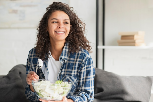 Schöne lächelnde frau, die salat isst