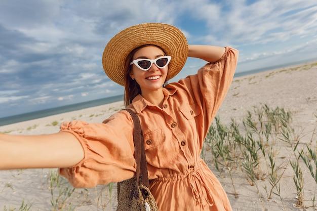 Schöne lächelnde frau, die selbstporträt macht und ferien nahe dem ozean genießt. trägt eine trendige retro-sonnenbrille und einen strohhut.
