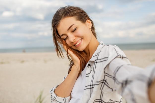 Schöne lächelnde frau, die selbstporträt macht und ferien nahe dem ozean genießt.