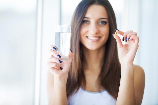 Schöne lächelnde frau, die vitamin-pille einnimmt