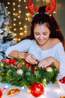 Schöne lächelnde frau, die weißes gestricktes kleid trägt, das weihnachtskranz im dekorierten raum macht.