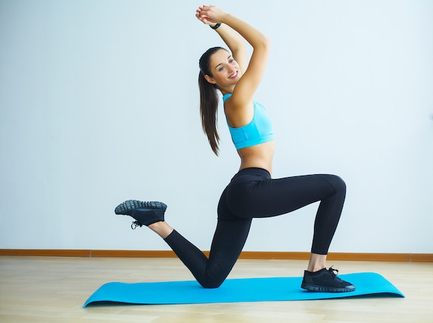 Schöne lächelnde frau, die zuhause yoga in der turnhalle tut