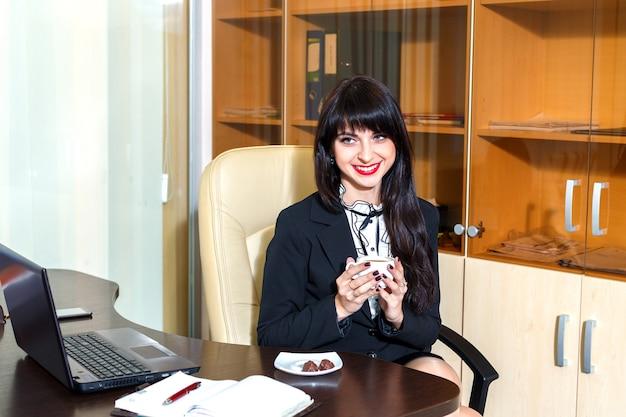 Schöne lächelnde frau im büro, das eine kappe des kaffees hält
