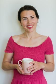 Schöne lächelnde frau im rosa kleid hält eine tasse in ihren händen.