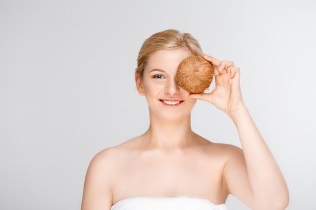Schöne lächelnde frau im spa, das kokosnuss hält