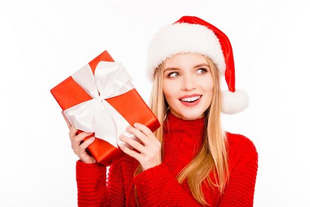 Schöne lächelnde frau im weihnachtsmannhut, der weihnachtsgeschenk hält