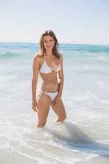 Schöne lächelnde frau im weißen bikini, der im meer steht