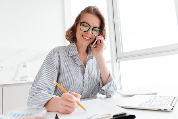 Schöne lächelnde frau in den gläsern, die auf handy sprechen, während sie mit dokumenten zu hause arbeiten