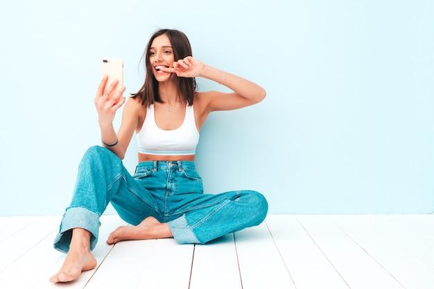 Schöne lächelnde frau in weißem jersey-top-shirt und jeans gekleidet. sorglos fröhliches model genießt ihren morgen