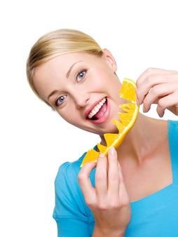 Schöne lächelnde frau isst die frische orange