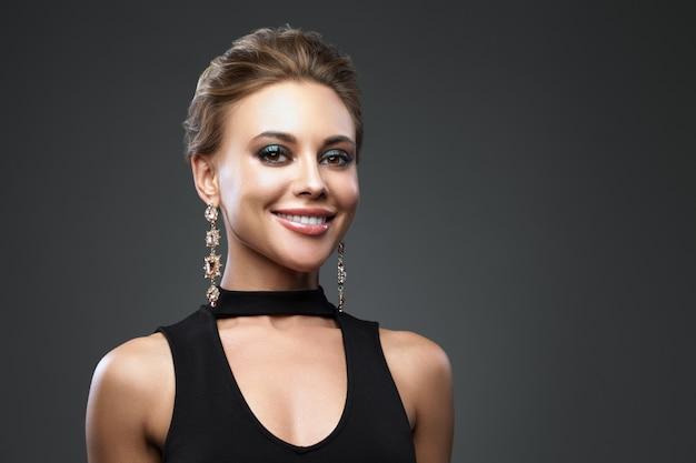 Schöne lächelnde frau mit abend make-up. schmuck und schönheit. modefoto