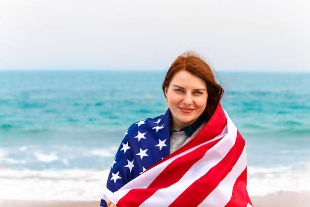 Schöne lächelnde frau mit amerikanischer flagge, die die kamera auf dem meer betrachtet