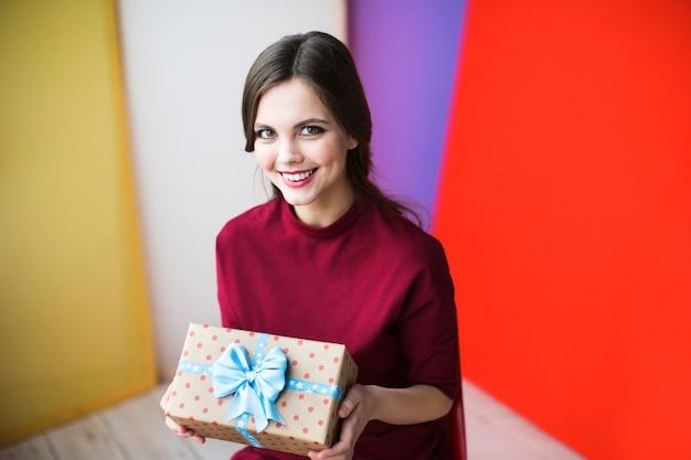 Schöne lächelnde frau mit einem geschenk
