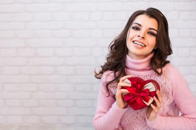 Schöne lächelnde frau mit einer geschenkbox in form des herzens. feier.