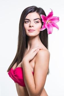 Schöne lächelnde frau mit einer lilie lokalisiert auf weißem hintergrund
