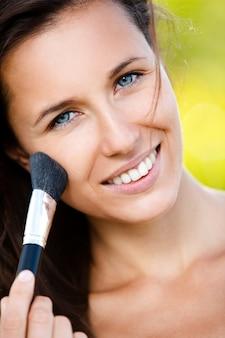 Schöne lächelnde frau mit make-up-pinsel