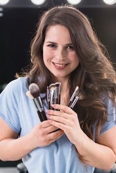 Schöne lächelnde frau mit make-upbürsten
