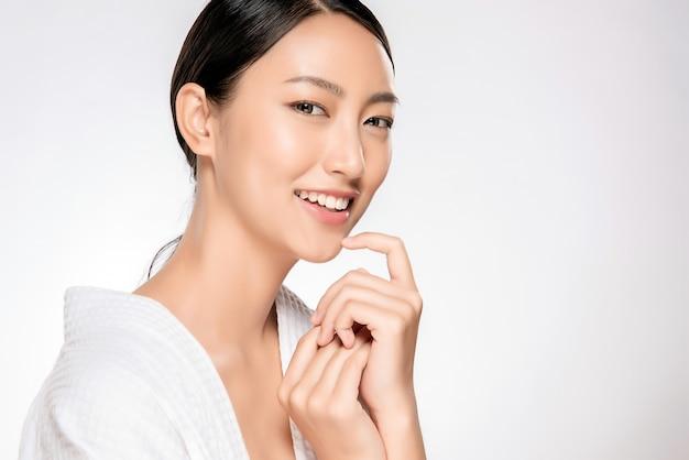 Schöne lächelnde frau mit natürlichem make-up, saubere haut