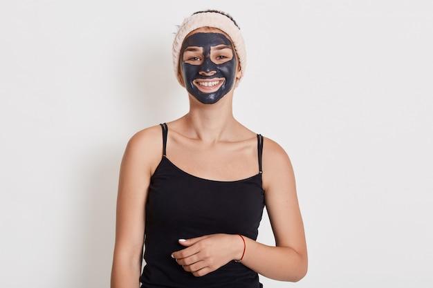 Schöne lächelnde frau mit schwarzer tongesichtsmaske auf gesicht, das gegen weiße wand mit charmantem lächeln steht, nettes mädchen, das kosmetische verfahren zu hause tut, sieht glücklich aus.