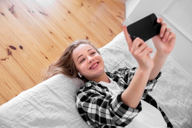 Schöne lächelnde frau mit smartphone