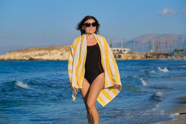 Schöne lächelnde frau mittleren alters, die entlang strand am sonnigen sommertag, meeressonnenuntergang szenischer ansichtsraum geht