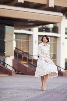 Schöne lächelnde frau mittleren alters im kleid, das an der stadtstraße an einem sonnigen tag geht.