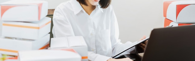 Schöne lächelnde frauenklammern unter verwendung der laptop-computers, die bestellung auf kunden- und online-lieferung überprüft.
