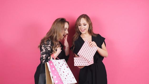 Schöne lächelnde freunde geben sich gegenseitig geschenke