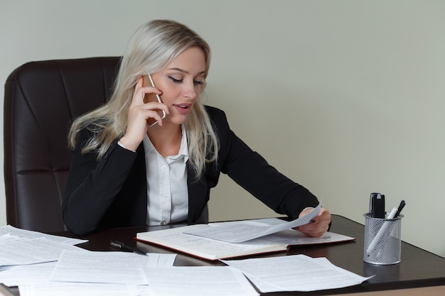 Schöne lächelnde geschäftsfrau, die an ihrem schreibtisch mit dokumenten arbeitet und am telefon spricht