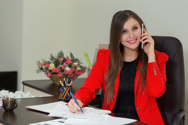 Schöne lächelnde geschäftsfrau, die an ihrem schreibtisch mit dokumenten arbeitet und am telefon spricht.