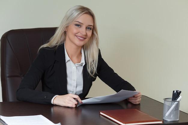 Schöne lächelnde geschäftsfrau, die an ihrem schreibtisch mit dokumenten arbeitet