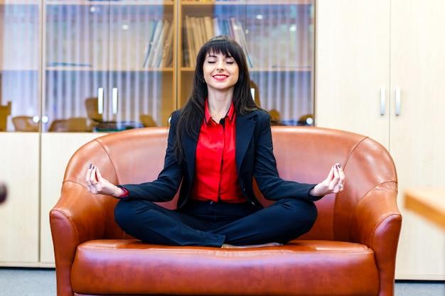 Schöne lächelnde geschäftsfrau, die auf einem sofa im lotussitz sitzt