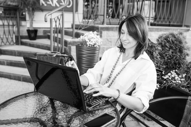 Schöne lächelnde geschäftsfrau, die im stadtcafé sitzt und mit ihrem laptop arbeitet. schwarzweiss-bild