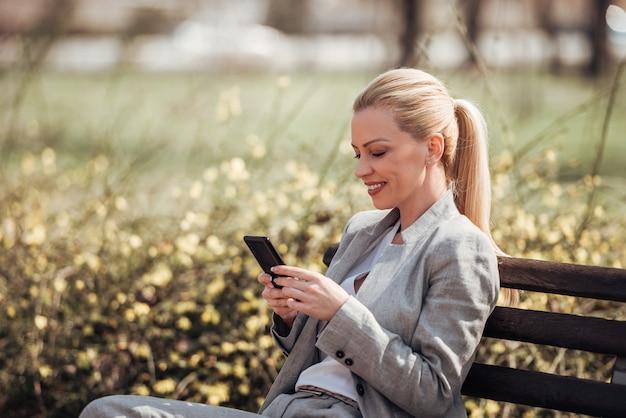 Schöne lächelnde geschäftsfrau, die smartphone beim sitzen auf einer bank im park verwendet.