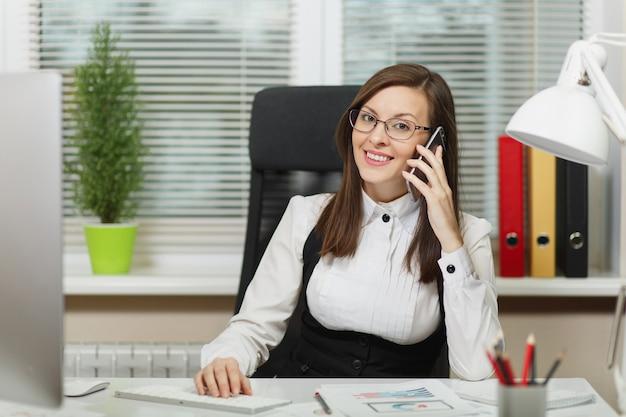 Schöne lächelnde geschäftsfrau in anzug und brille, die am schreibtisch sitzt, am modernen computer mit dokumenten im hellen büro arbeitet, mit dem handy spricht, angenehme gespräche führt