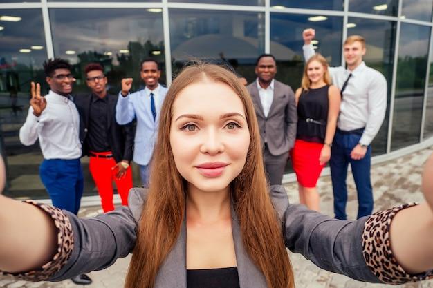 Schöne lächelnde geschäftsfrau mit afroamerikanischem und europäischem partner, einem erfolgreichen multirassischen geschäftsmännerteam, das zusammen selfie vor der kamera macht