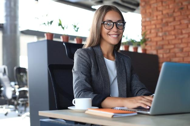 Schöne lächelnde geschäftsfrau sitzt im büro und betrachtet kamera.