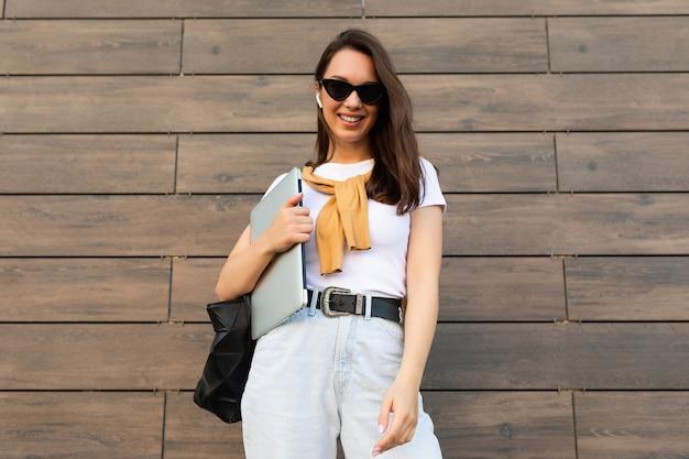 Schöne lächelnde, glückliche, charmante, faszinierende junge brünette, die die kamera mit computer-laptop und schwarzer sonnenbrille in weißem t-shirt und hellblauer jeans auf der straße in der nähe der braunen wand betrachtet.